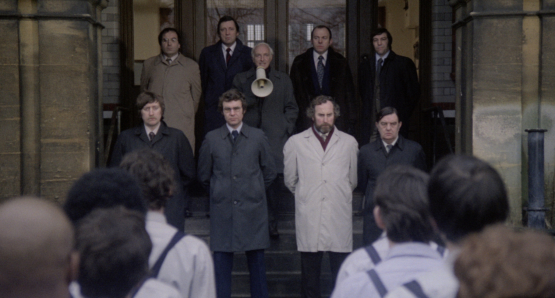 Peter Howell (with megaphone) as the Governor, flanked by his screws in Alan Clarke's SCUM