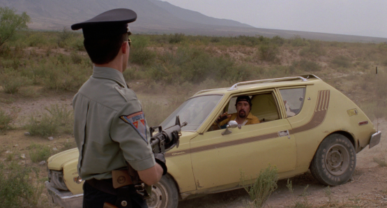 Roberto Sosa as the HIGHWAY PATROLMAN confronts a suspect in Alex Cox's 1991 drama.